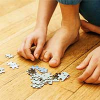 Little boy picking up puzzles